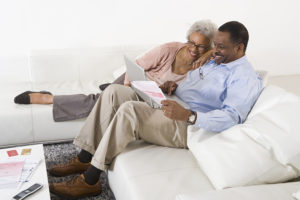 Senior African American couple paying bills online using laptop at home